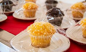 Muffins auf einem Servierwagen sind aufgrund der verschärften Hygienevorschriften einzeln mit Frischhaltefolie verpackt worden.