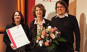 Ina Bielenberg, Geschäftsführerin des AdB, überreicht den ersten Preis an Christine Reich und Johannes Kreye von der Jugendbildungsstätte Kurt Löwenstein e. V.