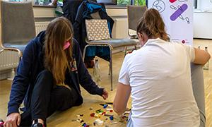In einem Seminarraum sitzen Menschen auf dem Boden und bauen mit Legosteinen.